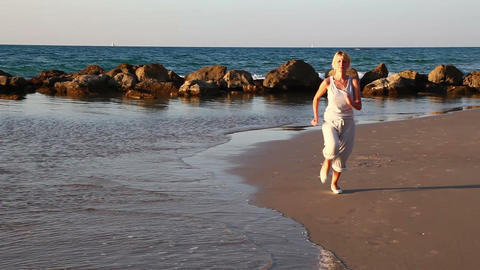 Girl jogging along a Beach Stock Video Footage