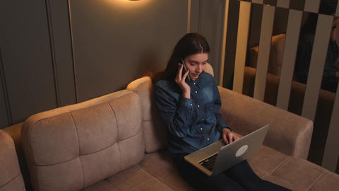 Smiling woman talking on a mobile phone while working on a laptop. A young woman Live Action