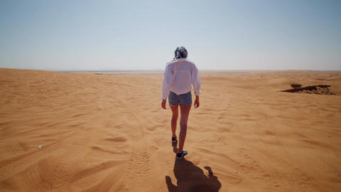 Following a young woman walking in the desert. Back view of young woman in shirt Live Action