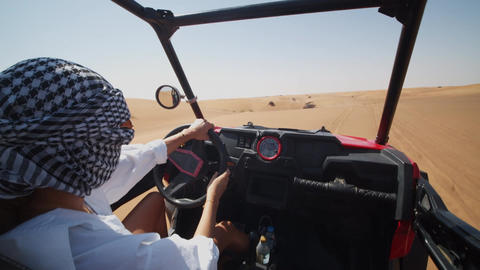 Young woman driving sand buggy on the sand dunes. Woman driving offroad vehicle Live Action