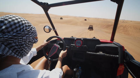 Woman driving a sand dune buggy in the desert. Pov of young woman with covered Live Action