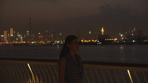 Woman walking on the pier by Dubai skyline at night. Attractive brunette woman Live Action
