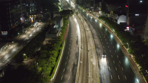 Low flying aerial dolly shot flying above empty multi lane highway through urban Live Action