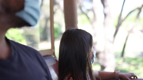 Little girl and her father wearing face masks in vehicle Live Action