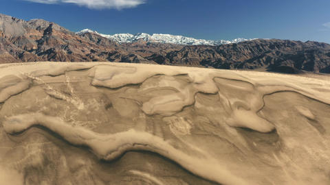 Scenic mountain landscape, desert nature 4K. Sand dunes aerial with snow summit Live Action