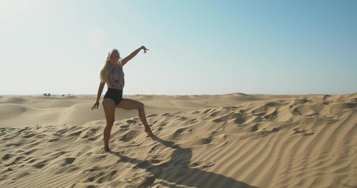 Pretty lady with blonde hair is dancing in the middle of the desert, UAE, 4k Live Action
