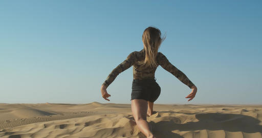 Rub al Khali desert, young lady is doing yoga and dancing on the sand, 4k Live Action