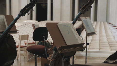 Close up dolly cellos and music stands on scene in classical style concert hall Live Action