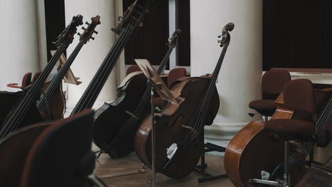 Dolly shot of few cellos on scene in classical music style concert hall Live Action