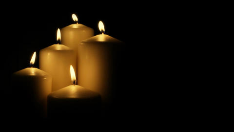 Five flickering candles on the black background Stock Video Footage
