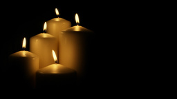 Five flickering candles on the black background Footage