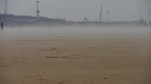 Wind Blowing Mist Over Beach,people Walking On Beach Against Mirage stock footage