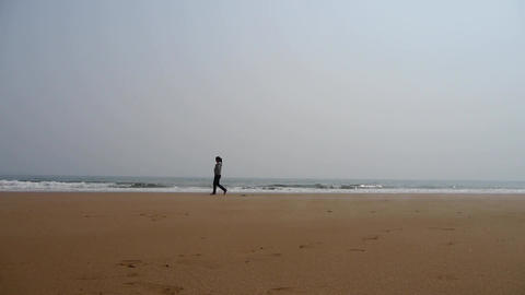 a girl alone walking on seaside Footage