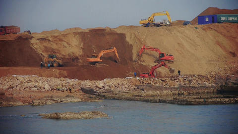 Excavator working & dumper truck on construction site near sea Footage