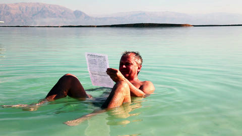 Man reads a relaxed lying in Dead Sea water Stock Video Footage