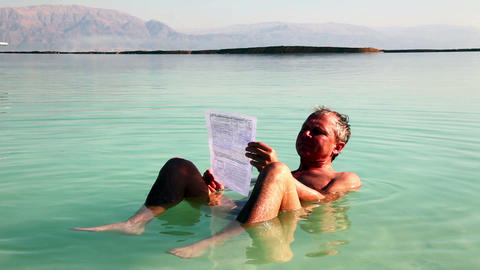 Man Reads A Relaxed Lying In Dead Sea Water stock footage