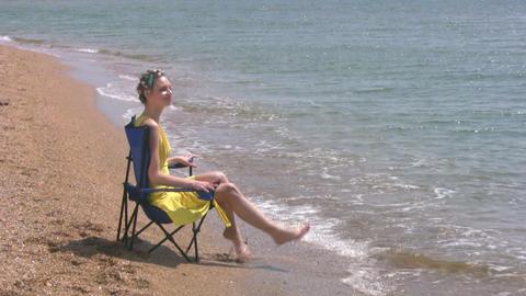 Beach, yellow dress, blue chair Stock Video Footage