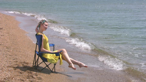 Beach, yellow dress, blue chair Footage