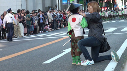 Woman fixes a young boy's hat during a traditional Footage
