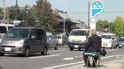 An elderly man waits for the bus in Kyoto, Japan Stock Video Footage