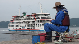 Japanese man fishing while ferry boat passes Footage