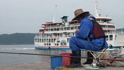 Japanese man fishing while ferry boat passes Stock Video Footage