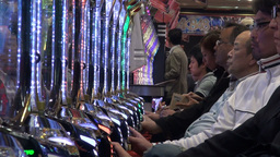 Japanese people play on 'pachinko' machines, fulfi Stock Video Footage
