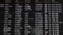 Schedule board in English and Japanese at Narita a Footage