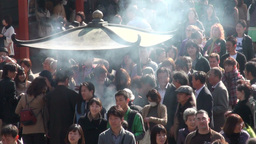 Crowds gather around urn that burns incense in Tok Stock Video Footage