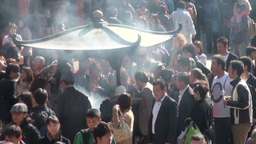 Crowds gather around urn that burns incense in Tok Footage