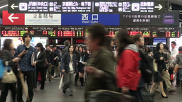 Passengers exit gates of a busy Kyoto train statio Footage