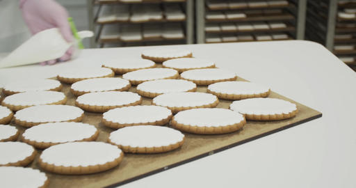 Confectioner is putting icing on gingerbread cookies and puts the sheet on shelf Live Action