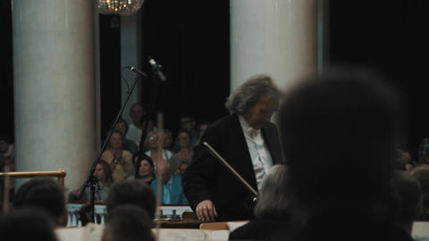 String orchestra lead musician bow to people in classic style music hall Live Action