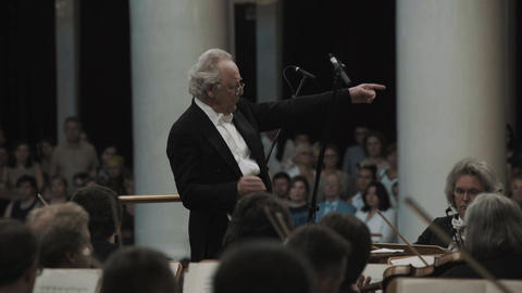 Silver-haired kapellmeister directing violin orchestra in classic music hall Live Action