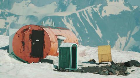 Orange metal drum tourist shelter at mountain peaks scenic landscape Live Action