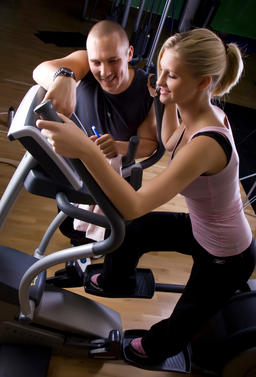 trainer with young woman on Stairmaster Foto