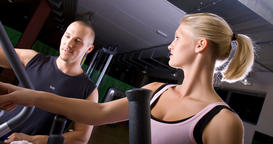 trainer with young woman on Stairmaster ภาพถ่าย