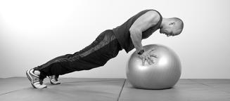 young man doing push-up on Swiss ball 사진