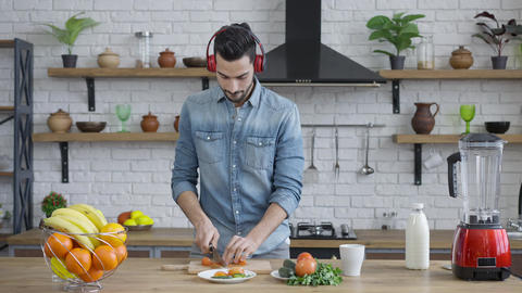 Handsome joyful Middle Eastern man in headphone cutting tomato for healthful Live Action