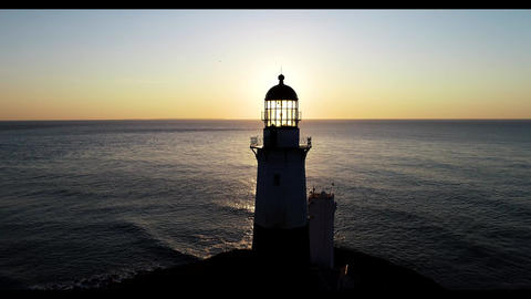 Scenic early morning sunrise behind lighthouse in Montauk New York aerial Live Action
