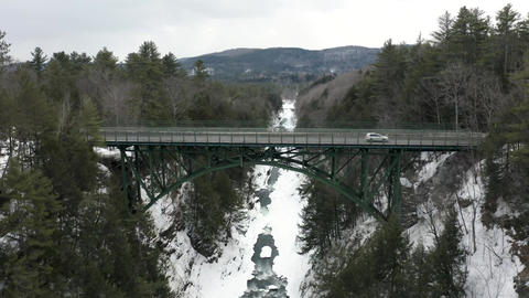 Vehicles driving on bridge over river in the winter with snow aerial Live Action