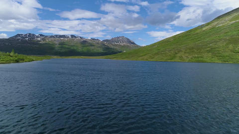 Aerial push in over lake near mountain in scenic Alaska Live Action