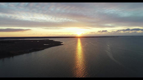 Scenic view of sun rising over calm waters of the Outer Barrier islands at dawn aerial Live Action