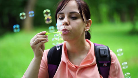 Young woman blowing bubbles on nature. Happy young brunette woman strolls in the Live Action
