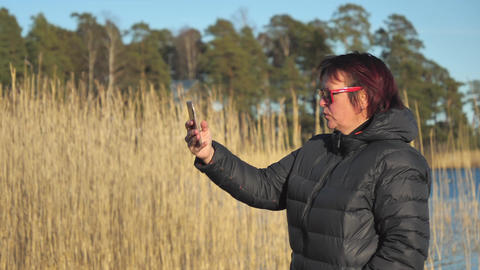 The view of the tall grasses on the back with the lady taking selfies in Finland Live Action