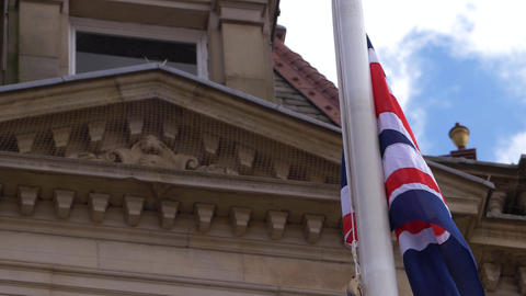 Union jack British flag flies outside town hall Live Action