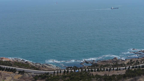 overlook waterfront & road from hill,ship traveling over sparkling waves Footage