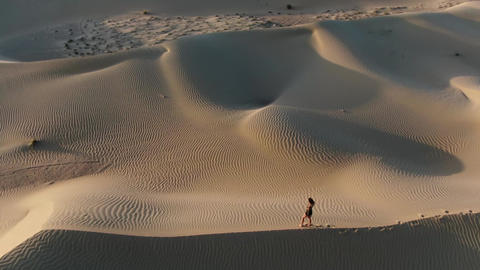 Drone footage of a young lady posing then walking on top of a sand dune, 4k Live Action
