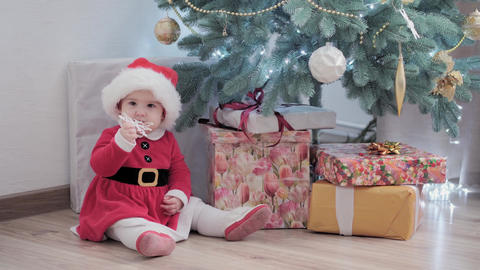authentic cute happy Joy chubby infant girl wearing santa hat and red dress Live Action