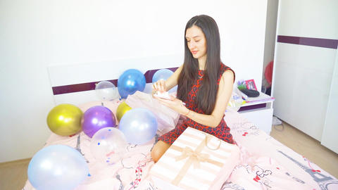 Beautiful woman with black hair sitting on bed and opens birthday presents Live Action